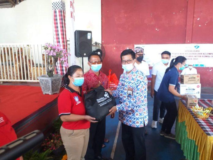 Kepala Perwakilan Wilayah BKKBN Provinsi Bali Agus Putro Proklamasi saat menyerahkan Bantuan kepada warga Seraya Barat, Jumat (7/5/2021)
